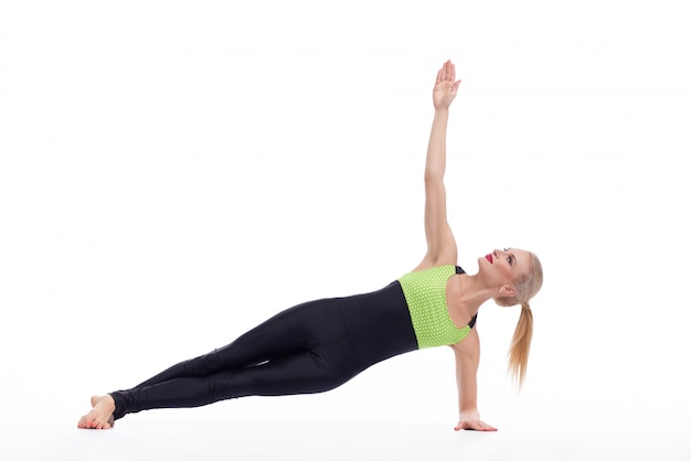 Mooie blonde vrouwelijke het praktizeren yoga die op wit wordt geïsoleerd