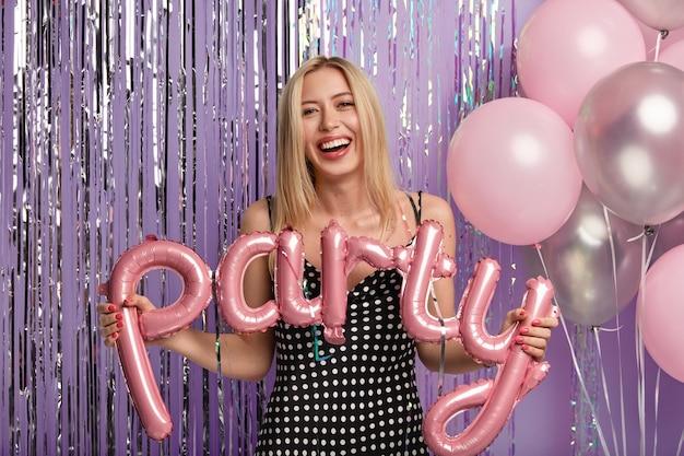 Mooie blonde vrouwelijke model met make-up, viert welkomstfeest, gekleed in zwarte polka dot jurk