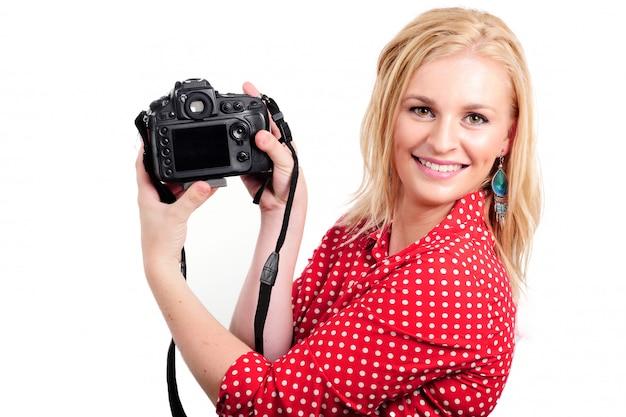 Mooie blonde vrouwenfotograaf met camera