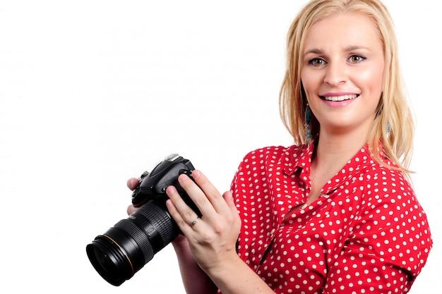 Mooie blonde vrouwenfotograaf met haar camera, op wit