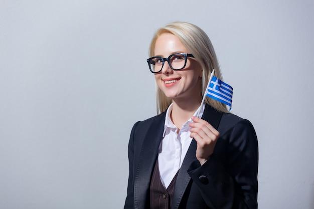 Mooie blonde zakenvrouw in pak met griekenland vlag op grijze achtergrond