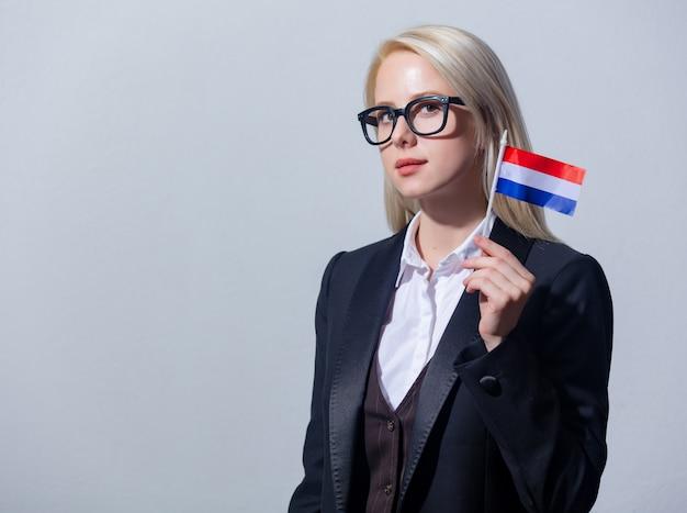 Mooie blonde zakenvrouw in pak met nederlandse vlag op een grijze achtergrond