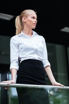 Mooie blonde zakenvrouw leunend op de glazen balustrade buitenshuis