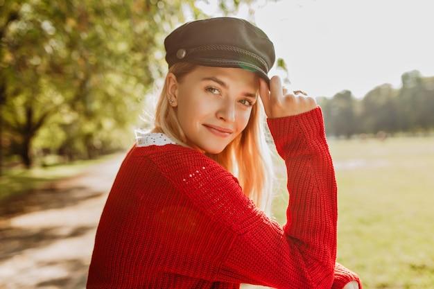Mooie blonde ziet er mooi uit in rode trui en trendy zwarte hoed in het park. glimlachend meisje geniet van zonnige herfstdag.