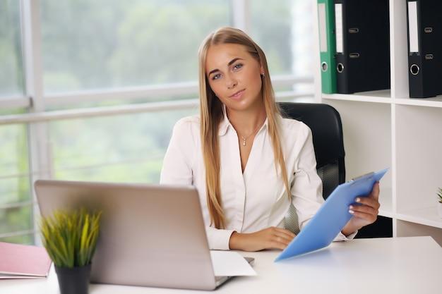 Mooie blonde zit op laptop, zakenvrouw
