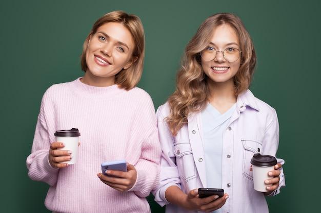 Mooie blonde zusters op een groene muur glimlachen naar de camera toothy en chatten terwijl ze een kopje koffie drinken