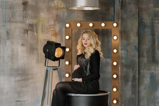 Mooie blonde zwangere vrouw in de studio