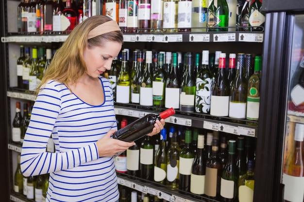 Mooie blondevrouw die een fles rode wijn houden
