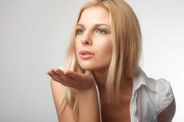 Mooie blondevrouw die een kus in studio verzenden