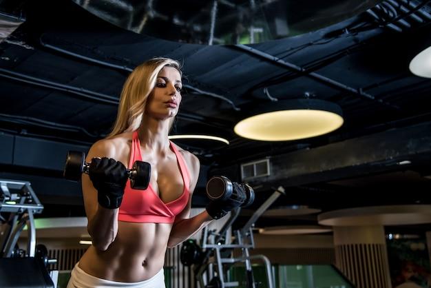 Mooie blondevrouw die in de gymnastiek uitwerken die gewichten opleiden opleiden