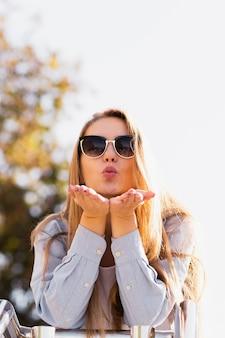 Mooie blondevrouw die kussen verzenden