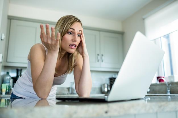 Mooie blondevrouw die laptop bekijken