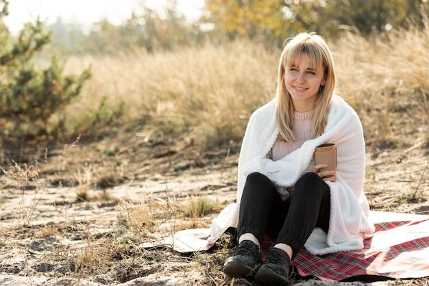 Mooie blondevrouw die met een deken behandelen