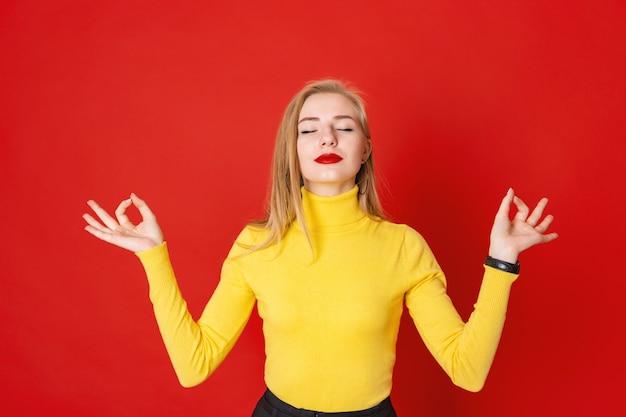 Mooie blondevrouw die met gesloten ogen op rode achtergrond mediteren.