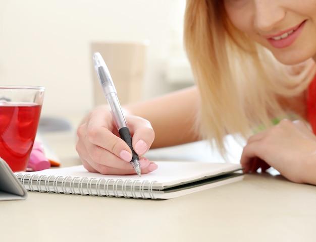 Mooie blondevrouw die op een blocnote schrijven