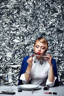 Mooie blondevrouw die samenstelling doen bij dinerlijst tegen van zilveren conceptuele achtergrond