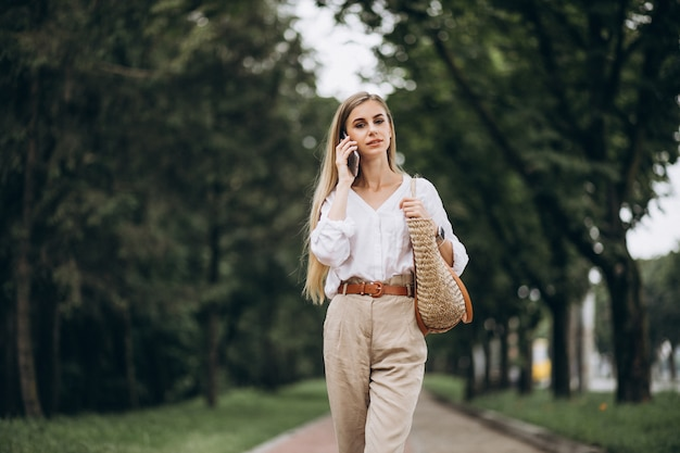 Mooie blondevrouw die telefoon buiten in park met behulp van