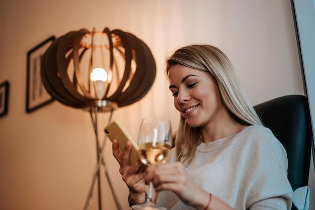 Mooie blondevrouw die telefoon met behulp van terwijl het genieten van van glas witte wijn in de avond.
