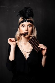Mooie blondevrouw in de jaren 20kleren met chocoladeplak