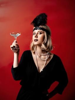 Mooie blondevrouw in de jaren 20kleren met cocktail op donkere achtergrond