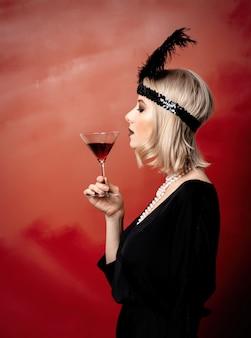 Mooie blondevrouw in de jaren 20kleren met cocktail
