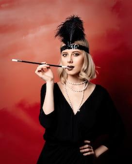 Mooie blondevrouw in de jaren 20kleren met rokende pijp op rode achtergrond