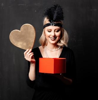 Mooie blondevrouw in de jaren 20kleren met valentine day-gift