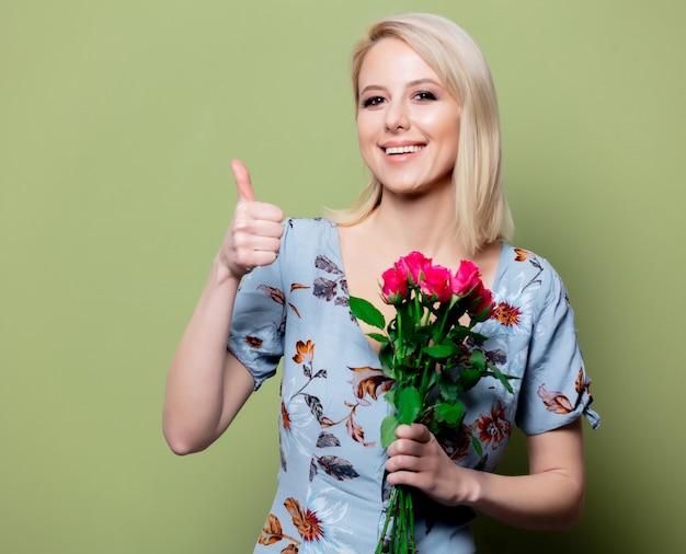 Mooie blondevrouw in kleding met rozen op groene muur