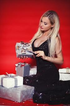 Mooie blondevrouw in lange zwarte kleding met giftdozen en dalende confettien op de rode geïsoleerde achtergrond