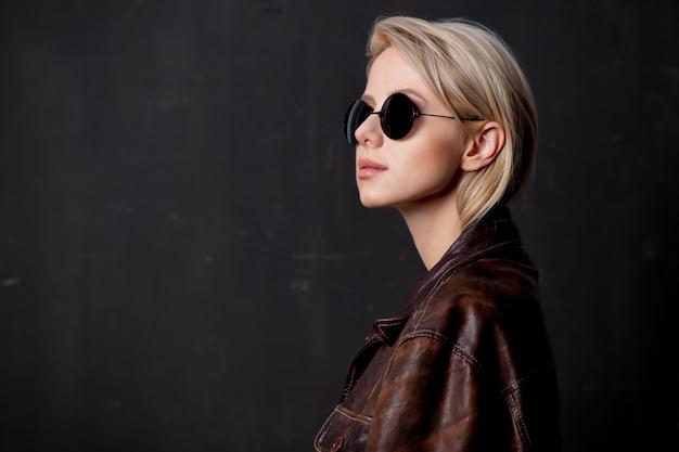 Mooie blondevrouw in zonnebril en stijljasje