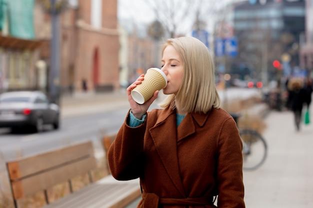 Mooie blondevrouw met kop van koffie op stadsstraat