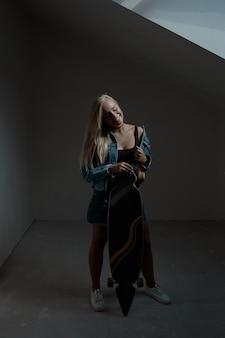 Mooie blondevrouw met longboard in donkere ruimte