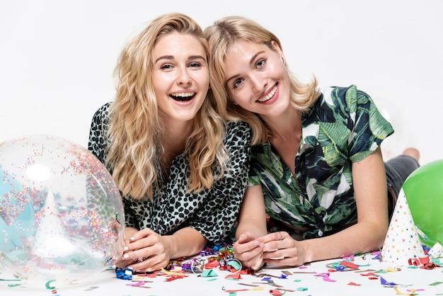 Mooie blondevrouwen die door ballons worden omringd