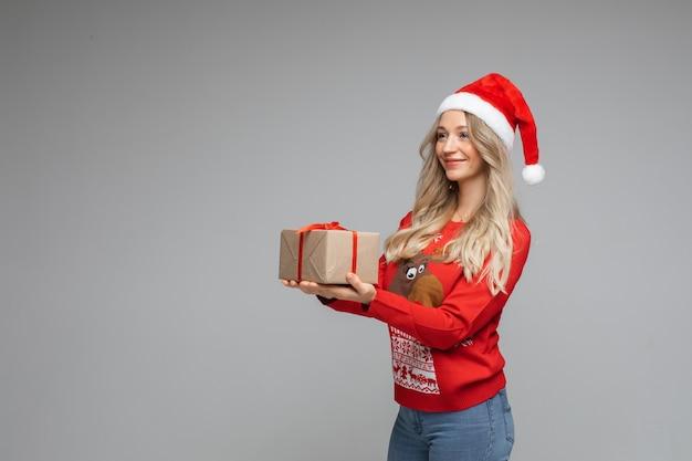 Mooie blondie met kerstcadeau in handen.