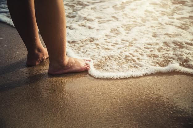 Mooie blote voeten op het zandstrand.