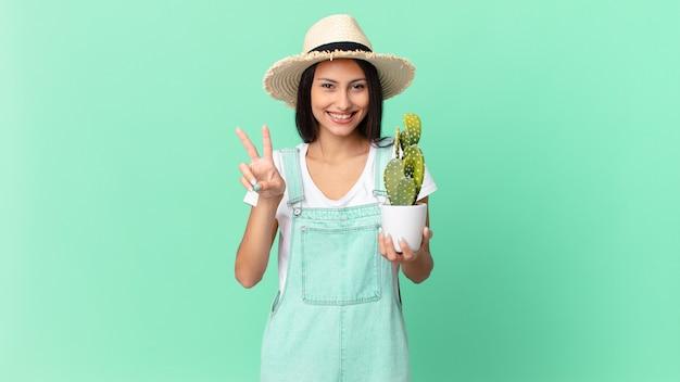 Mooie boerenvrouw die lacht en er gelukkig uitziet, gebaart naar overwinning of vrede en een cactus vasthoudt