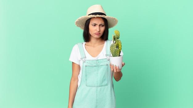 Mooie boerenvrouw die zich verdrietig, overstuur of boos voelt en opzij kijkt en een cactus vasthoudt