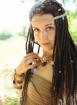 Mooie boho-stijl vrouw met dreadlocks portret, tegen zonnig zomerveld