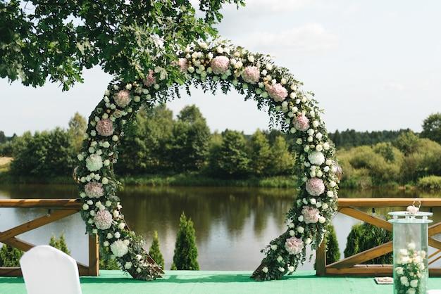 Mooie boog voor huwelijksceremonie, op natuurlijk landschap met uitzicht op het meer