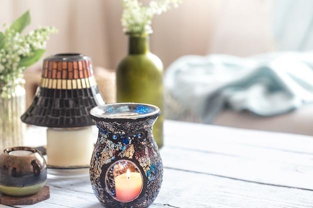 Mooie brandende kaarsen met flessen op witte lijst