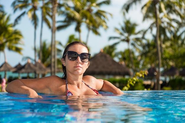 Mooie braziliaanse vrouw die van vakantievakantie geniet bij luxueus hotelresort aan het strand met zwembad en tropisch landschap dichtbij het strand