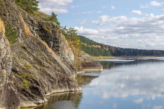 Mooie brede herfstrivier tussen bossen en rotsachtige kusten. een rustige en stille plek met herfstkleuren. weerspiegeling van wolken in het water bij mooi weer