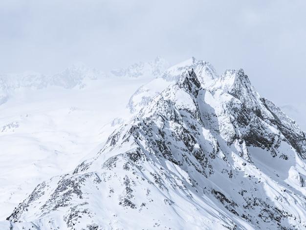 Mooie brede opname van bergen bedekt met sneeuw onder een mistige hemel