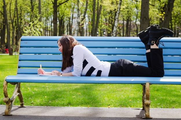 Mooie brinette meisje zittend op een bankje, dromen en haar plannen schrijven in een notitieblok, ontspannen in een park op een zonnige lentedag