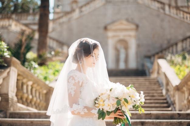 Mooie bruid bedekt met een sluier met bruidsboeket op de trap