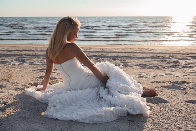 Mooie bruid dichtbij overzeese kust die mooie huwelijkskleding draagt.