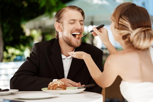 Mooie bruid die haar bruidegom met croissant in koffie voeden.