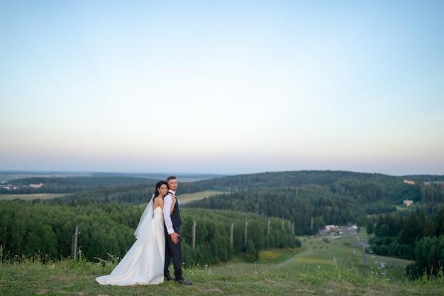 Mooie bruid die haar bruidegom van achter bovenop berg in de avond koestert.