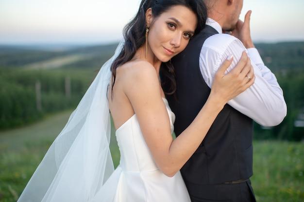 Mooie bruid die haar bruidegom van achter openlucht koestert.
