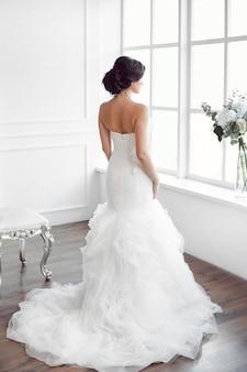 Mooie bruid die venster bekijkt. studio die van achteren in witte ruimte is ontsproten.